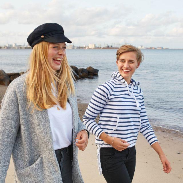Zwei Studentinnen gehen am Strand spazieren.