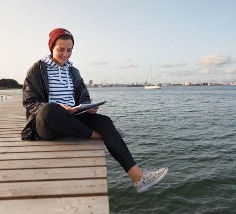 Studentin sitzt auf einem Steg am Meer