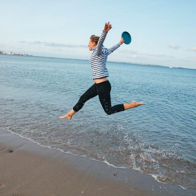 Studentin Hannah springt am Strand in die Luft.