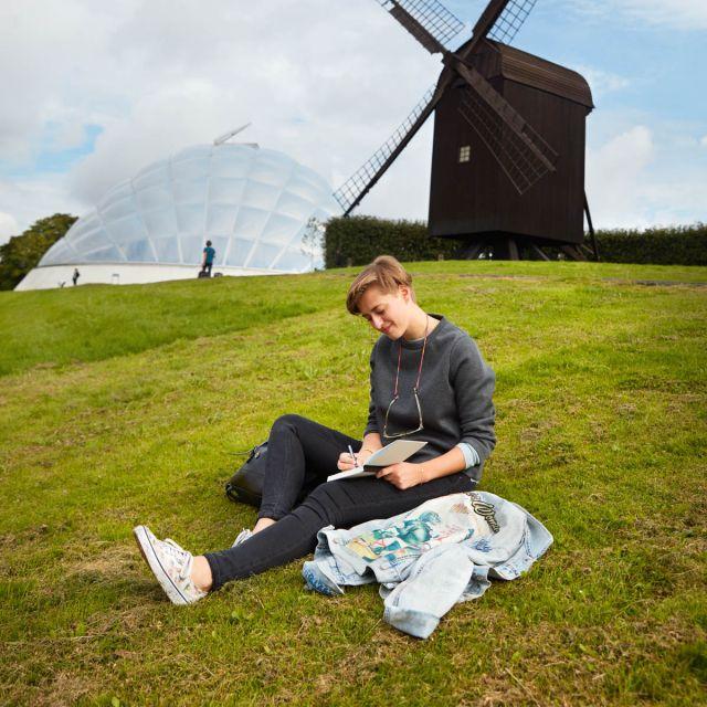 Studentin Hannah sitzt vor einer Windmühle in Aarhusund lernt.