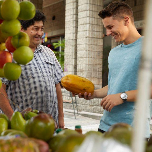 Student Viktor kauft eine Papaya an einem Straßenstand.