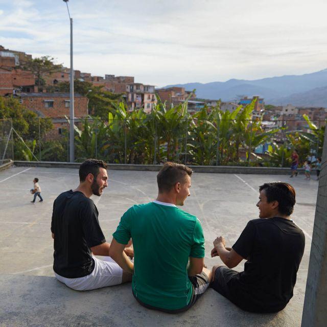 Viktor und seine Freunde sitzen vor einem Sportplatz in Medellín.