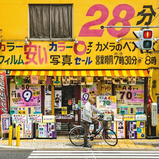 Ein Handygeschäft in Tokio mit gelber, voll geschriebener Wand.