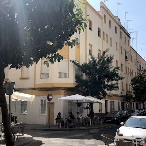 Ein an der Ecke stehendes Wohngebäude im typisch spanischen Baustil. Vor dem Haus steht ein kleiner Baum, worunter sich die Stühle und Tische eine sRestaurants befinden.