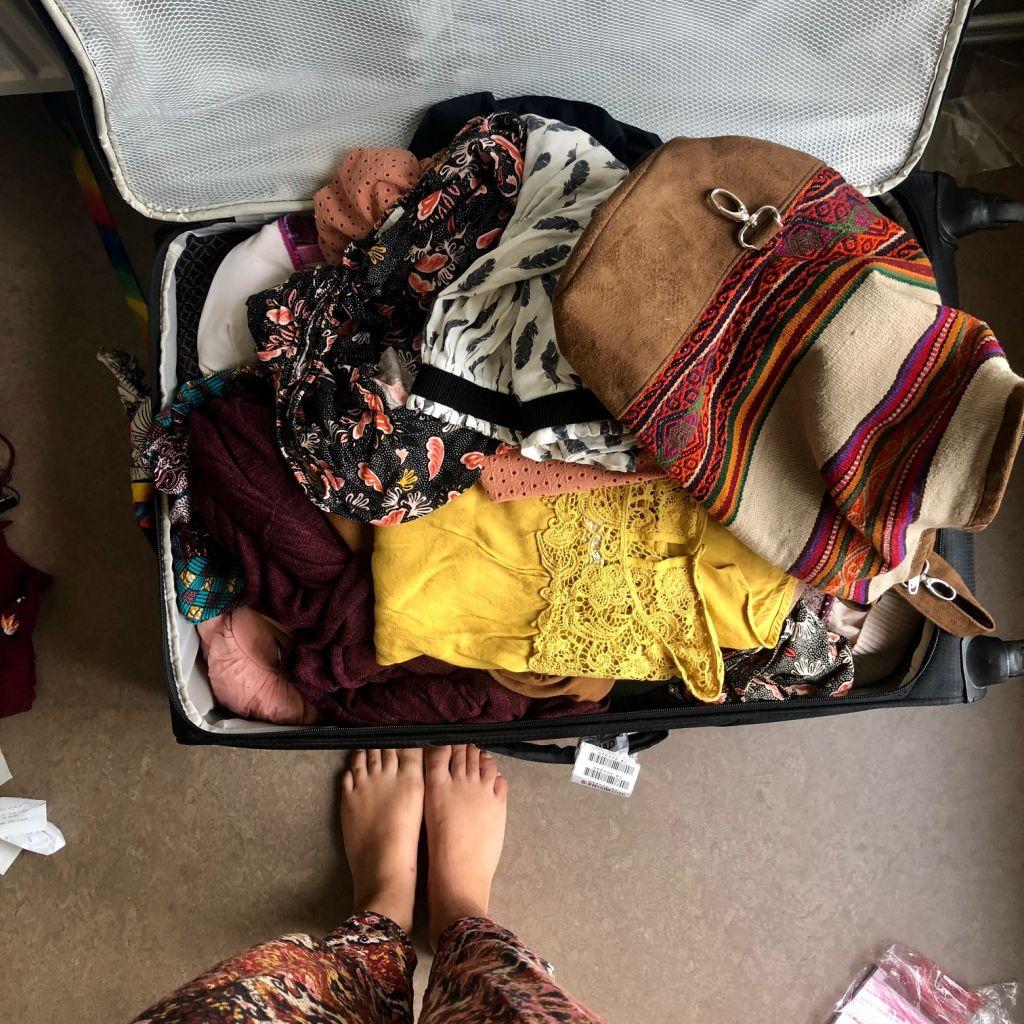 gefüllter Koffer, bunte Kleidung, Chaos