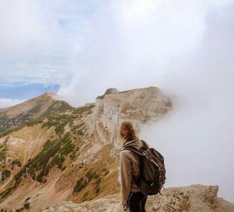 Eine Studentin blickt auf ein Gebirge im italienischen Trentino.