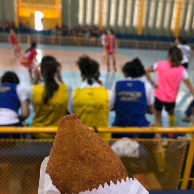 Coxinha im Vordergrund und Fußballspiel im Hintergrund