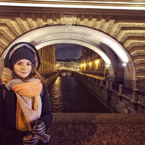 Studentin Saskia steht in dicker Winterkleidung vor einer Brücke in St. Petersburg.