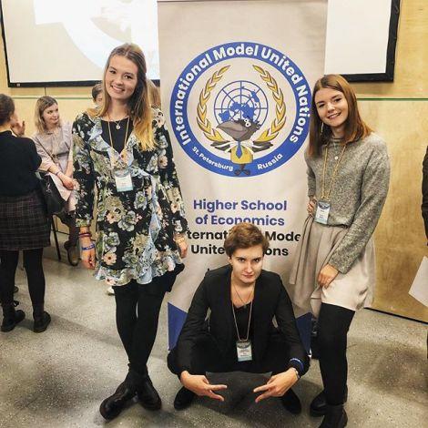 Drei Studentinnen vor dem Schild der Model-UN in St.Petersburg.