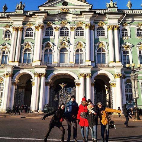 Eine Gruppe junger Menschen steht vor dem in grün und gold verzierten Ermitage in St. Petersburg.