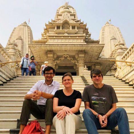 Simon und seine Eltern sitzen auf einer Treppe vor einem Tempel in Indien.