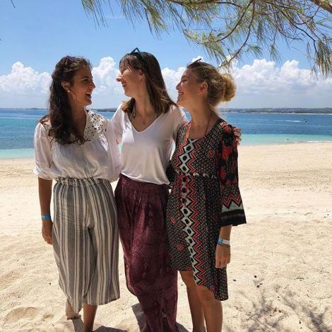 Drei junge Frauen stehen lachend am Strand.