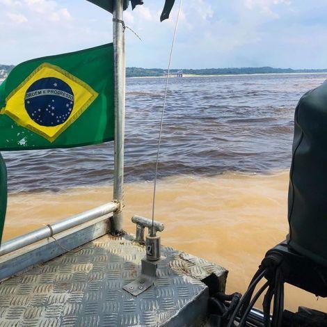 Ein Boot auf dem Amazonas. Im Vordergrund weht eine brasilianische Flagge.