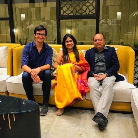 Student Simon sitzt mit einem indischen Paar auf einem gelben Sofa.