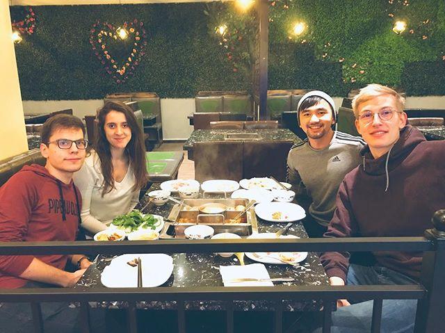 Eine Gruppe junger Menschen sitzt an einem Tisch um einen chinesischen Feuertopf.