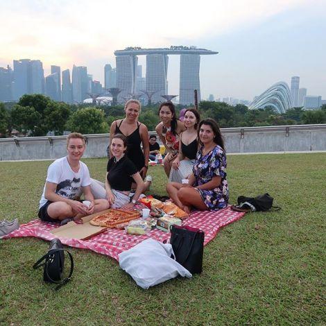 Eine Gruppe junger Menschen beim Picknick vor der Skyline von Singapur.