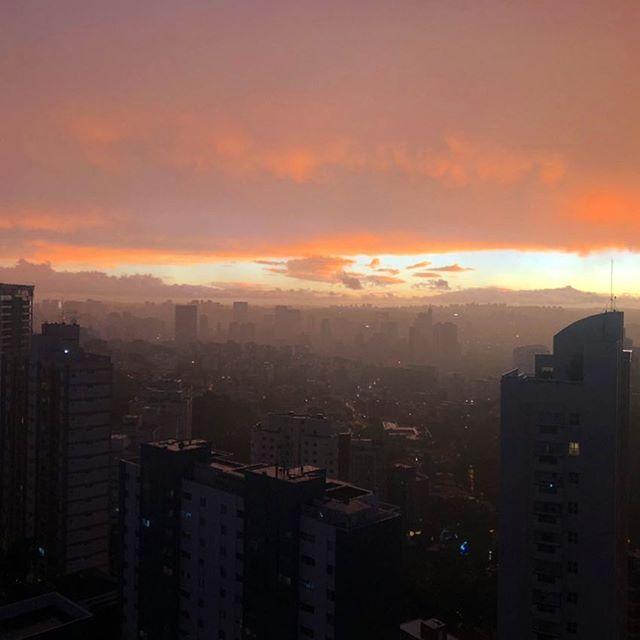 Blick über die Skyline von Sao Paolo. Im Hintergrund geht die Sonne unter und es sind Berge zu sehen.