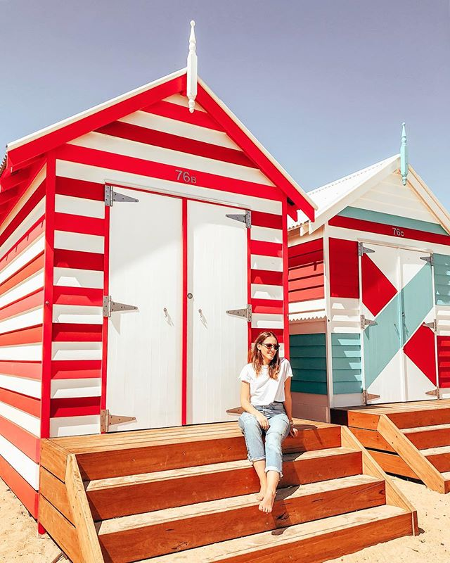 Studentin Larissa sitzt vor knallbunten Bade-Hütten am Strand in Australien.