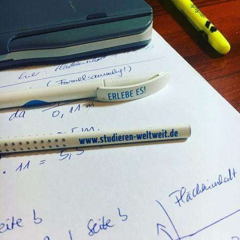 """Ein Taschenrechner, ein Textmarker und Stifte von """"studieren-weltweit"""" auf einem Schreibtisch mit Mathe-Aufgaben."""