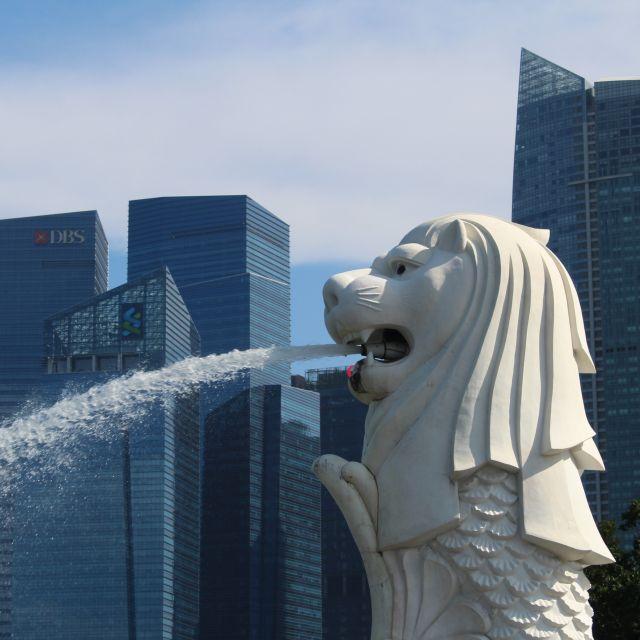 Der Merlion vor den blauen Wolkenkratzern