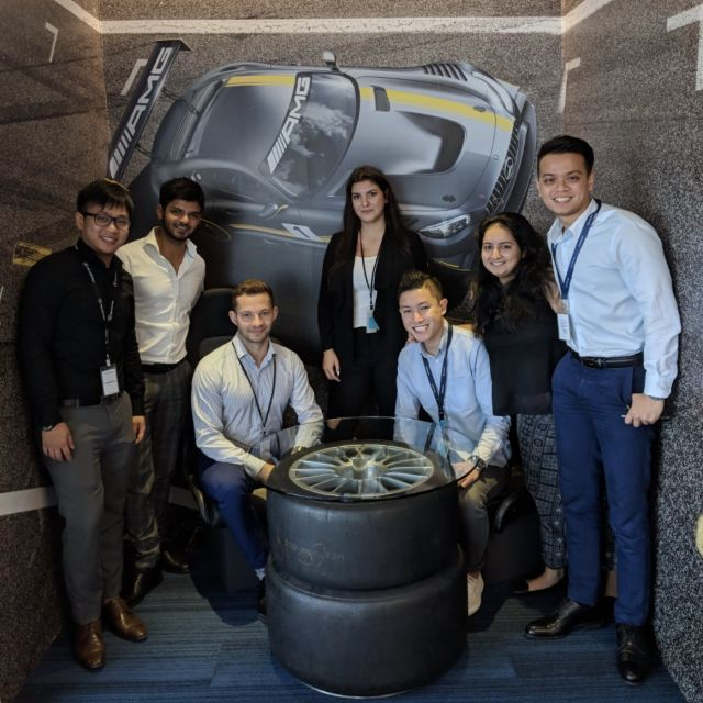 7 Personen vor einer Wand mit AMG-Wandbild
