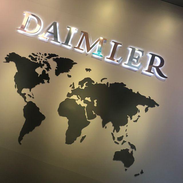 Daimler-Schriftzug über einer Weltkarte an der Wand