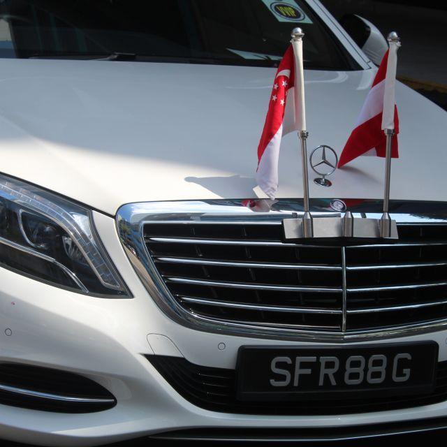 Weißer Mercedes mit zwei österreichischen Flaggen auf der Mototrhaube