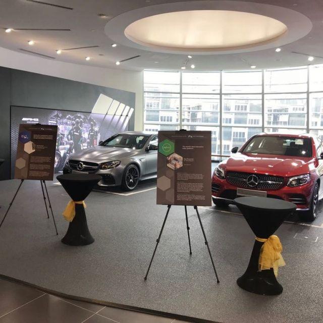 Zwei Mercedes und Messestände im Vordergrund