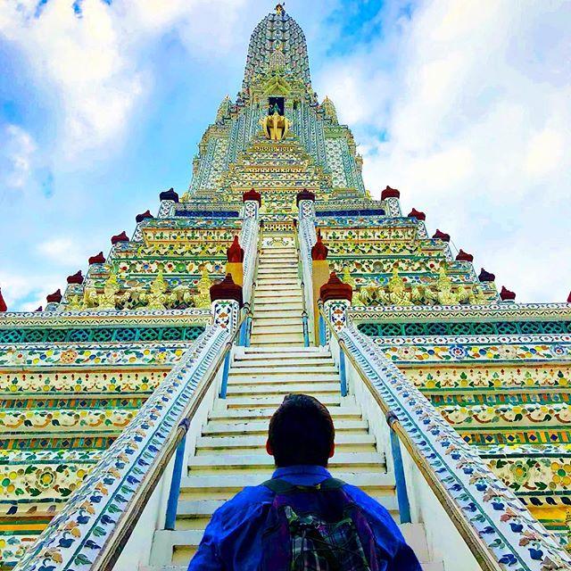 Student Simon steht am Fuß einer Treppe zu einem bunt verzierten Tempel in Bangkok.