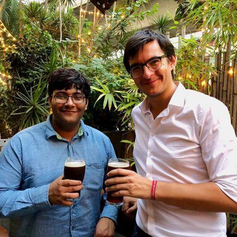 Simon und ein indischer Freund stoßen mit einem Bier auf ihr Wiedersehen an.