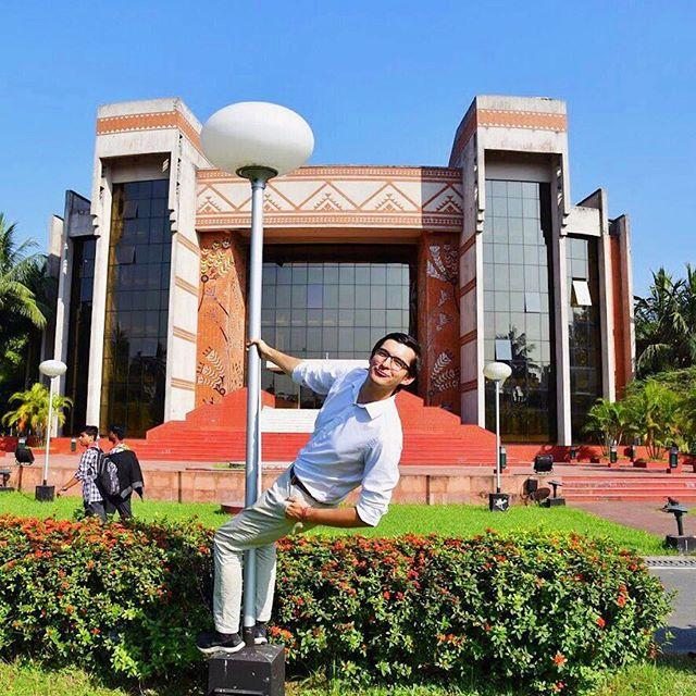 Student Simon albert an einer Straßenlaterne auf dem Campus seiner Uni in Indien herum.
