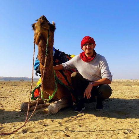 Student Simon hockt neben einem Kamel in der indischen Wüste. Der Himmel ist blau und klar.