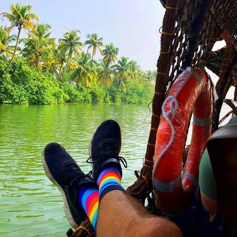 Blick von einem Boot auf den indischen Dschungel. Im Vordergrund liegen die Beine von Student Simon, er trägt Turnschuhe und bunte Socken.