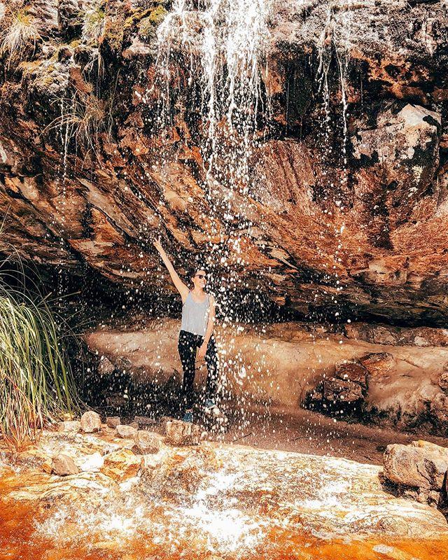 Studentin Larissa steht unter einem Wasserfall in Australien und hebt die Hand zum Peace-Zeichen.