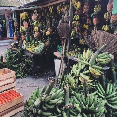 Ein Obst-Stand in Tansania, an dem man viele Bananen, Ananas und andere Früchte kaufen kann.