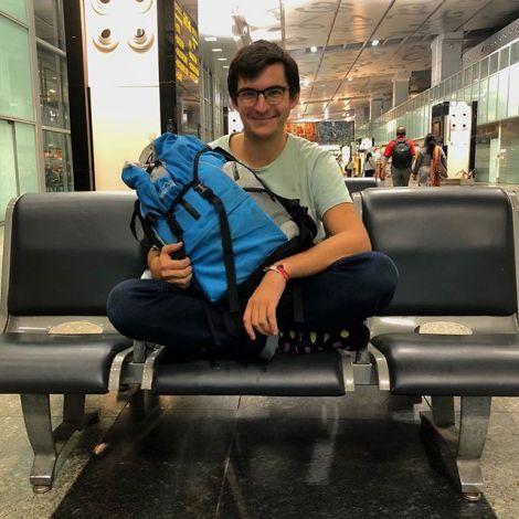Student Simon in einer Bahnhofswartehalle. Auf seinem Schoß hat er seinen blauen Rucksack.