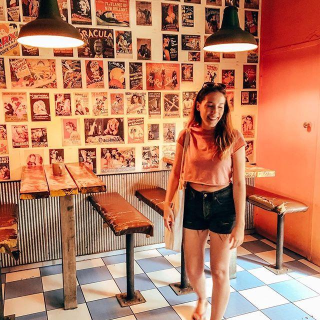 Studentin Larissa steht in einem Café in Alice Springs. Hinter ihr an der Wand hängen alte Filmplakate.