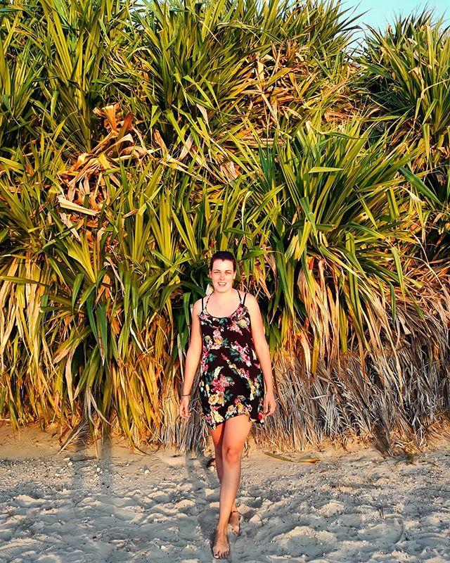 Studentin Laura im Sommerkleid vor einem riesigen Palmengebüsch am Strand.