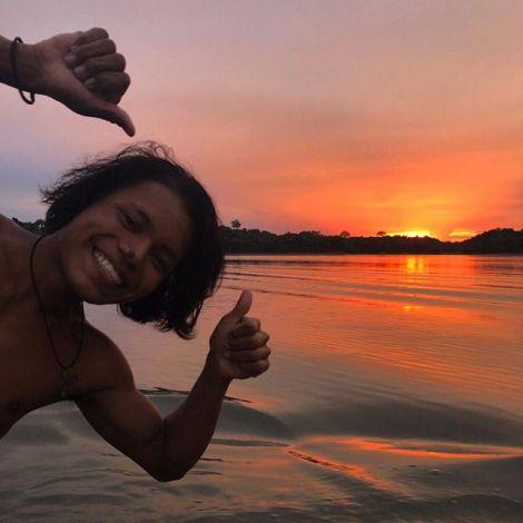 Sonnenuntergang im Amazonas, im Vordergrund ist ein fröhlich schauender junger Mann in einem Boot zu sehen.