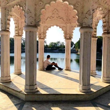 Student Simon sitzt unter einem reich verzierten Pavillon an einem der vielen See im indischen Udaipur.