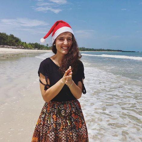Anastasia steht am Strand in Tansania und trägt dabei eine Nikolausmütze.