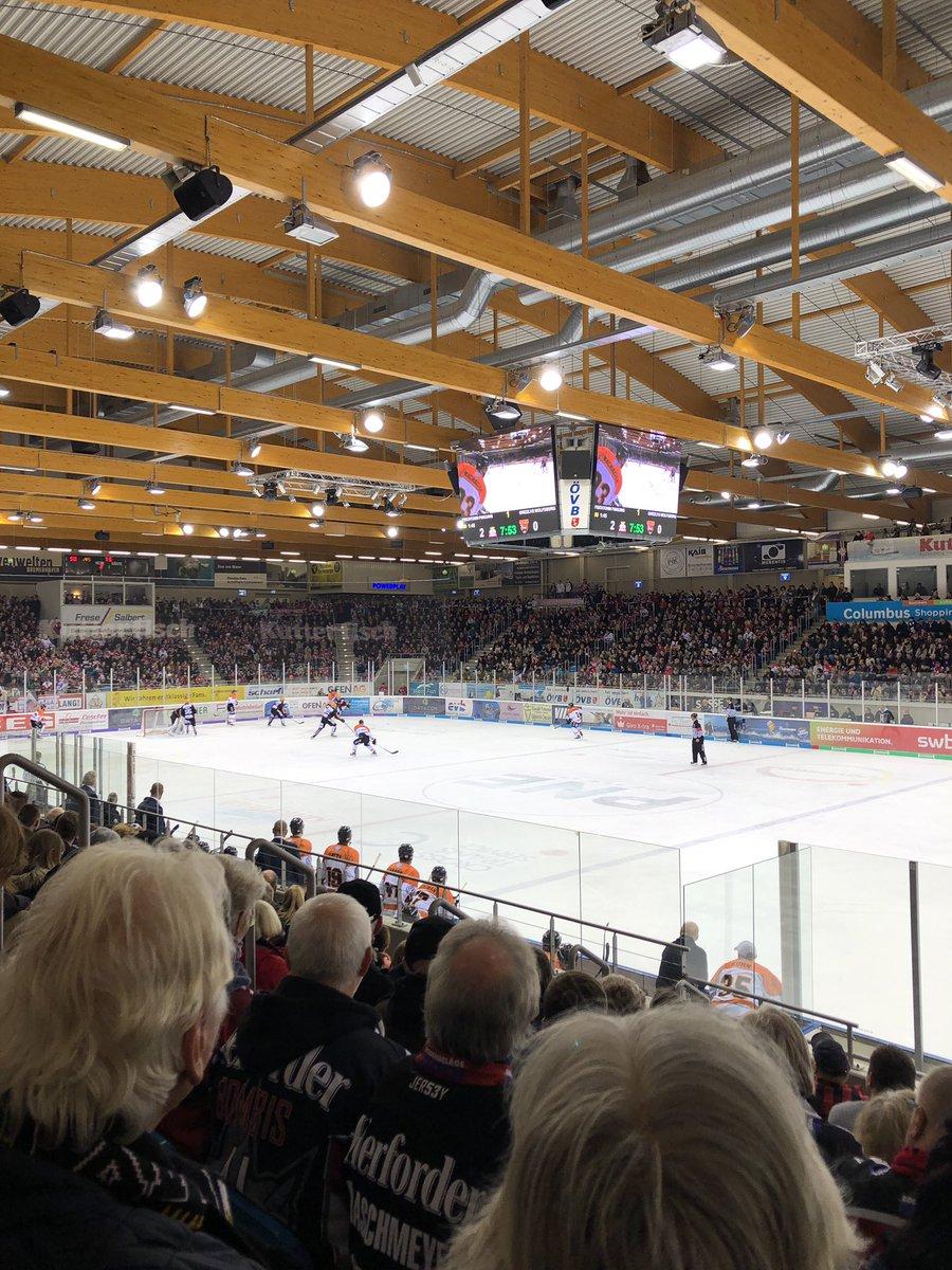 Ein Eishockeystadium, auf dem Feld läuft ein Spiel.