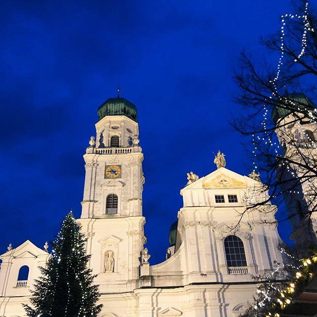 Eine Kirche in Passau. Davor steht ein beleuchteter Weihnachtsbaum.