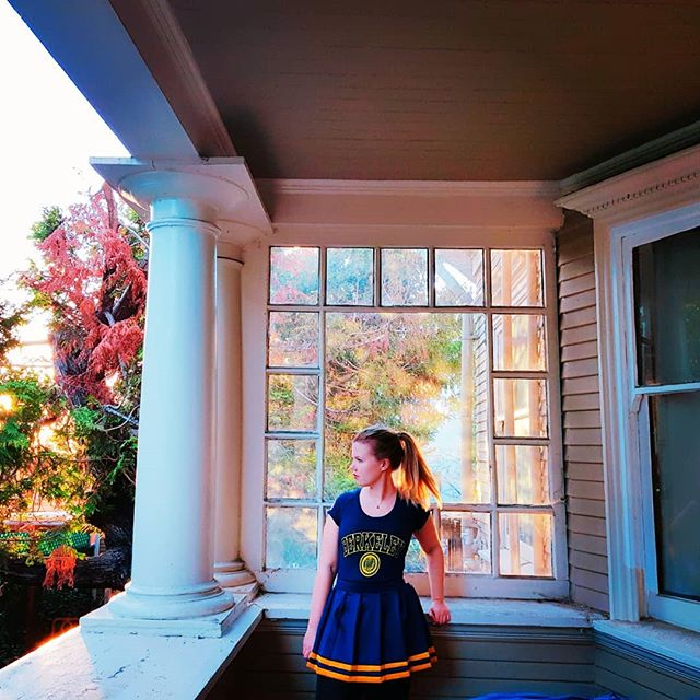 Eine Studentin steht am Fenster. Sie trägt ein T-Shirt der Berkeley-Universität und einen Rock in blau und gelb, den Farben der Uni.
