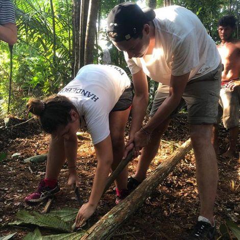 Studentin Lene gemeinsam mit einem jungen Mann beim Gärtnern im Amazonas.