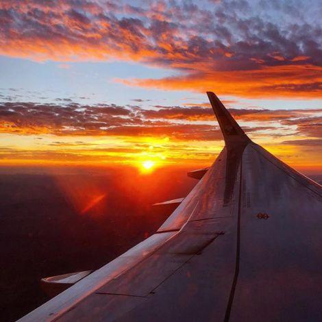 Blick aus dem Flugzeugfenster. Man sieht eine Tragfläche und im Hintergrund die Sonne untergehen.