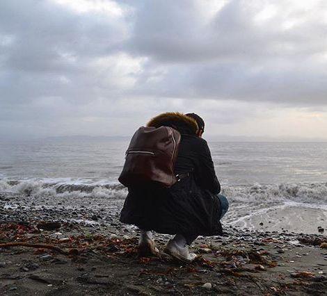 Student Max hockt nachdenklich am Strand in Kanada.