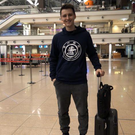 Nicholas am Hamburger Flughafen. Er trängt einen Pulli seiner chinesischen Uni.