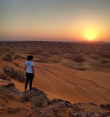 Studentin Laura steht auf einer Düne in der Wüste und beobachtet den Sonnenuntergang im Hintergrund.