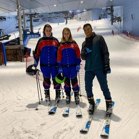 Laura steht mit einer Freundin und einem Freund am unteren Ende einer Abfahrt in einer Skihalle in den vereinigten arabischen Emiraten.
